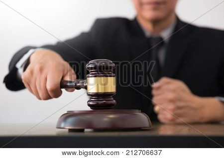 Male Judge Lawyer In A Courtroom Striking The Gavel On Sounding Block In His Office
