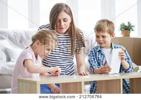 Attractive young mother and her cute children enjoying each others company while gathered together in living room and assembling furniture