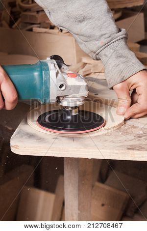 Worker polishing wood table where carpenter hands sanding a wood with electric sander