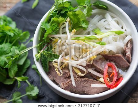 Traditional Vietnamese soup- pho in a white bowl with beef and rice noodles, mint and cilantro, green onion, chili, bean sprouts and lime on a dark blue napkin.  Asian food. Top view