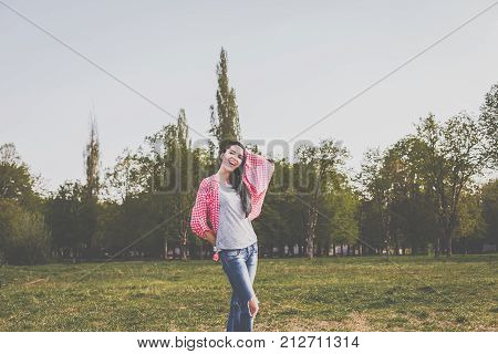 Beautiful hipster girl in red plaid shirt, grey t-shirt and ripped blue jeans in a casual style smiling in green park
