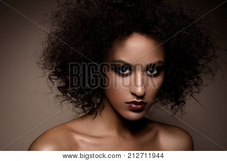 Fashion studio portrait of beautiful african american woman with perfect smooth glowing mulatto skin, smoky eyes make up