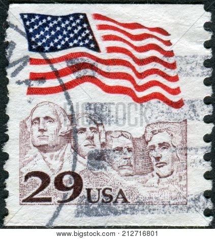 USA - CIRCA 1991: Postage stamp printed in the USA shows the national flag over Mount Rushmore National Memorial circa 1991