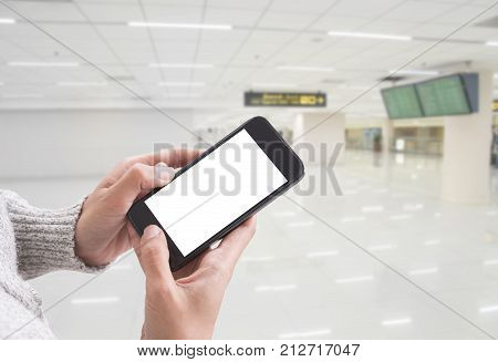 hand holding smart phone screen isolated with blurred abstract hallway background.
