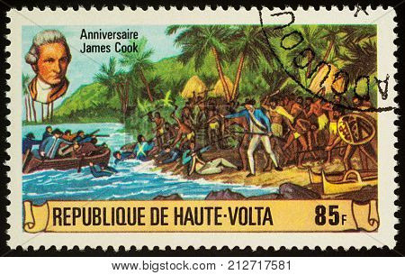 Moscow Russia - November 08 2017: A stamp printed in Upper Volta shows landing of James Cook's team on a tropical island series