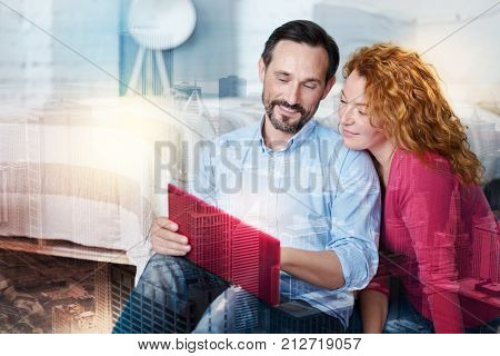 Need your opinion. Pleasant young man sitting on the floor next to his wife, using a laptop and showing the results of his work to her, asking for her opinion
