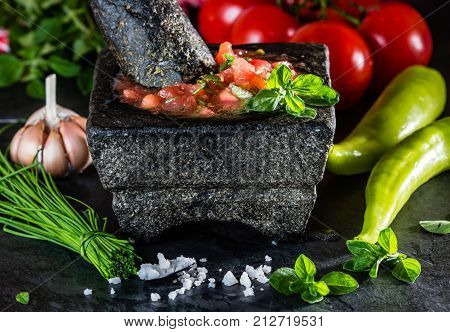 Traditional Latin American mexican Tomato sauce salsa, chilean chancho en piedra in stone mortar and ingredients tomatoes, chile, garlic, onion, sea salt on dark slate stone background