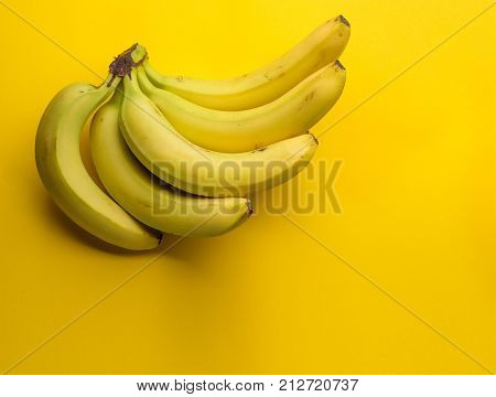 Tasty fresh ripe banana on yellow background with copy space.