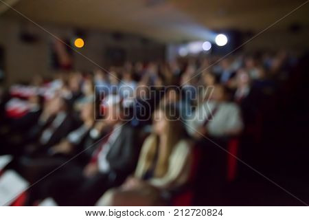 Blurry background of people watching movie in the movie theater.