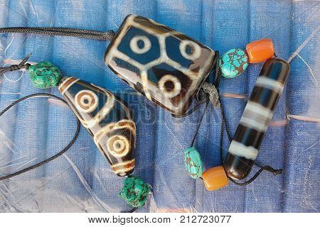 Tibetan Stones Amulets Defenders Dzi: Stones Strung On Ropes And Decorated With Blue Beads Turquoise