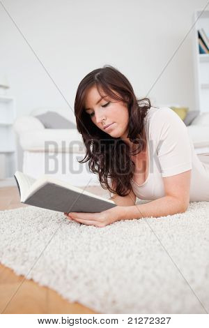 Junge schöne Frau, ein Buch zu lesen, beim liegen auf einem Teppich