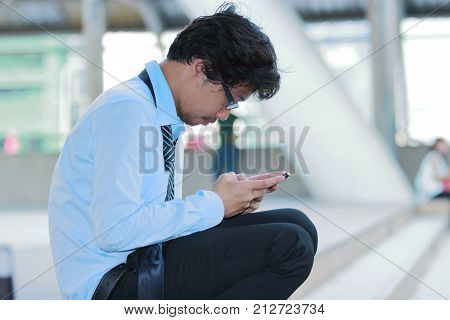 Side view of unemployed stressed young Asian man looking mobile smart phone for find job. Unemployment concept.