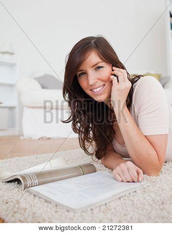 Junge charmante Frauen, die eine Zeitschrift lesen, beim liegen auf einem Teppich
