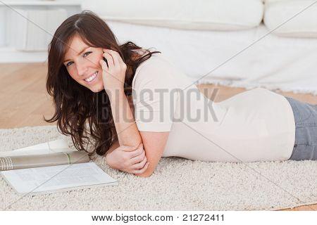 Junge schöne Frau, die eine Zeitschrift lesen, beim liegen auf einem Teppich
