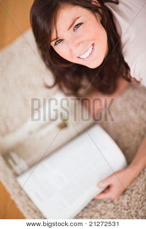 Süße Frau, eine Zeitschrift lesen, beim liegen auf einem Teppich