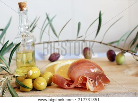 Still life with Spanish a pata negra ham olives and olive oil in a bottle on a wooden cutting board