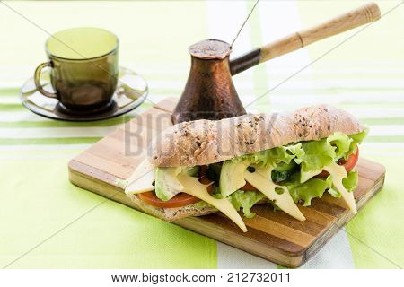 fitness sandwich with avocado and cheese and black coffee on wooden board