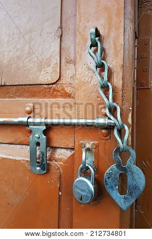 Brown wooden door on which a vintage latch a metal lock and an old door chain unusual interior elements.