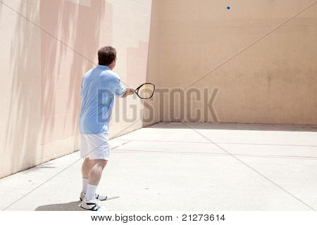 Mid adult man playing racquetball on a hot day.