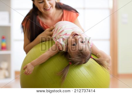 Cute child girl stretching on pilates fitness ball with mother in gym
