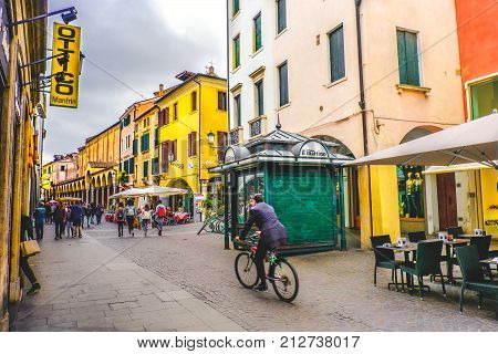 daily life in Italy. A business man in bicycle crossing one of the central roads of Padua passing by a green newsstand kiosk on the street (Padova Italy 24 Apr 2017)