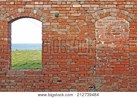 Old brick wall with one window opening and one bricked up