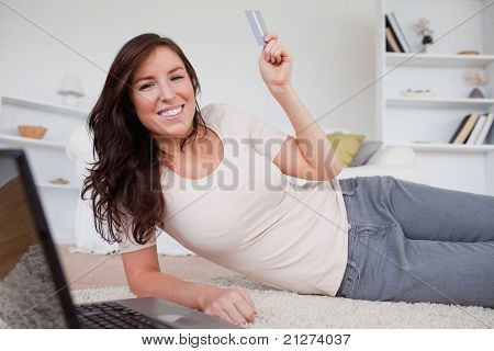 Good Looking Brunette Female Making A Payment With A Credit Card On The Internet While Lying On A Ca