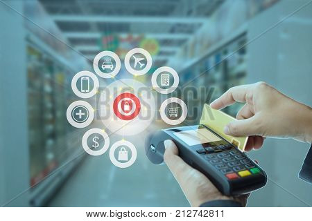 Female cashier swiping credit card with a handheld reader and icon of payment service via credit card security concept