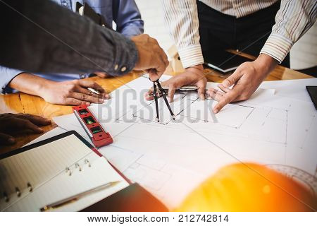 Consultation between colleagues engineering team to check the blueprint used to build commercial buildings for joint ventures.