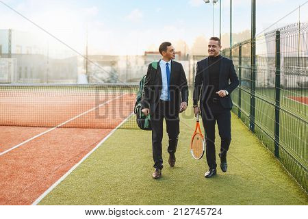 Business, partnership and sport. Front view successful businessman walking and chatting after a tennis set, wearing suits and tennis equipment.  Business partners practicing sport together. Mentoring.