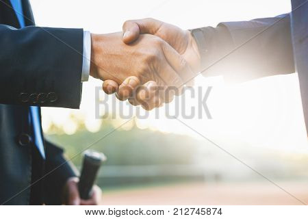 Business handshake. Two businessmen shaking hands while standing outdoors holding tennis rackets. Men shaking hands during a meeting on outdoors background, success, dealing, greeting and partner.