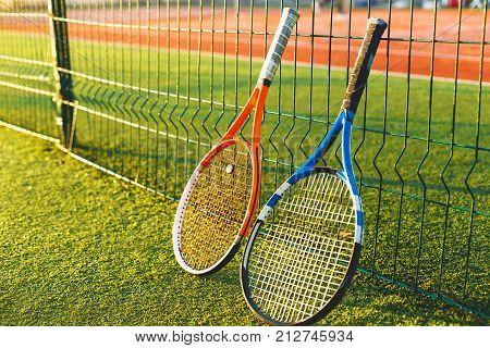 Tennis ball and rackets under sunlight on tennis court. Equipment for playing tennis on grass.  Close-up tennis rackets.