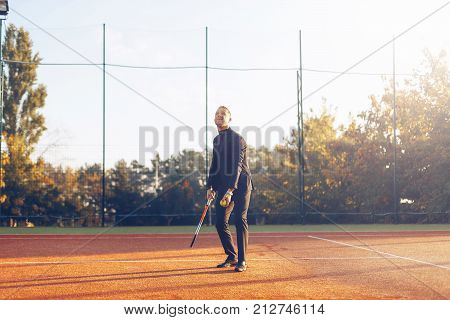 Portrait of confident middle aged businessman holding tennis racket ready to serve against tennis court background. A portrait of a tennis player wearing suit with a racket.