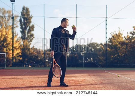 Portrait athletic businessman holding tennis racket ready to serve against tennis court background. A portrait of a tennis player wearing suit with a racket.