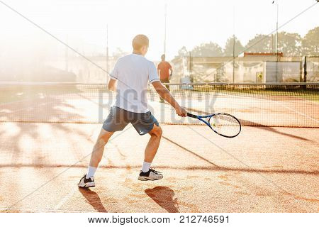 Man playing tennis in the morning in sunlight. Picture of handsome young man on tennis court. Man throwing tennis ball. Forest area as background