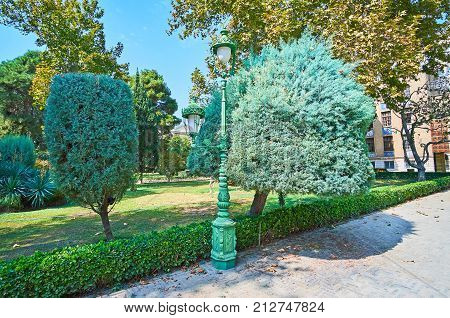 The walk in shade of Golestan garden with trimmed bushes coniferous trees and palms and the old fashioned streetlights Tehran Iran.