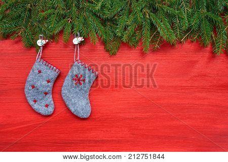 Red Christmas Background. Christmas Fir Tree And Christmas Socks On Red Wooden Background. Copy Spac