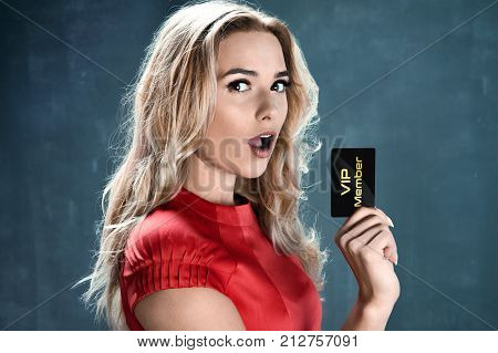 Delighted beautiful woman holding vip member card