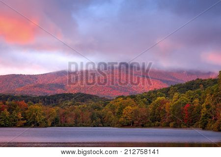 The fiery colors of autumn drape the Blue Ridge Mountains along the Blue Ridge Parkway in North Carolina near the town of Blowing Rock. This was taken at Price Lake.