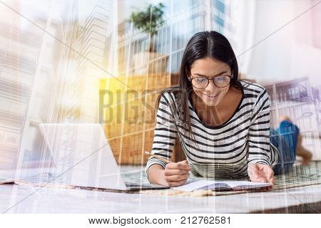 Diligent person. Enthusiastic reliable diligent student looking happy while doing her homework near a modern laptop and smiling