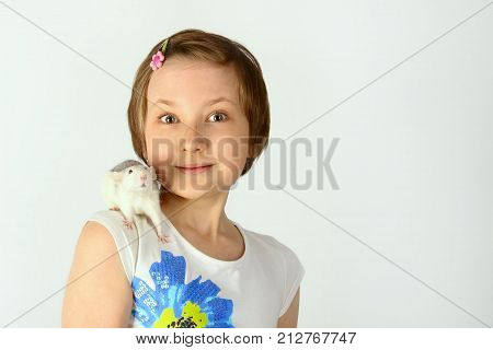 Shot of a happy little girl holding a Rat. Portrait of a little girl playing with her pet rat.   Portrait of a pretty young girl with her pet  rat.