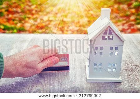 Mini home model and plastic credit card in man's hand. Payments for house. Buy house concept. Cost of home concept