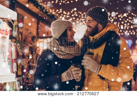 Having fun together at a christmas fairy with snowfall. Young cheerful couple is having a walk with hot drinks enjoying dressed warm looking at each other and laugh snowflakes all around