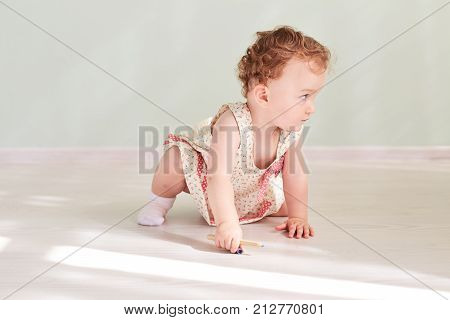 Adorable little baby girl laughing, smiling, creeping amp. playing in the studio wearing  dress