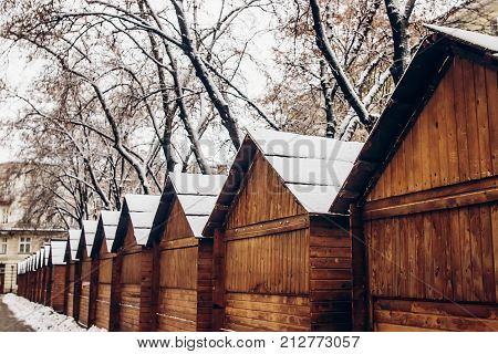 Wooden Cabins In Snow For Christmas Market. Snowy Town Square In Lviv. European City Preparing For W