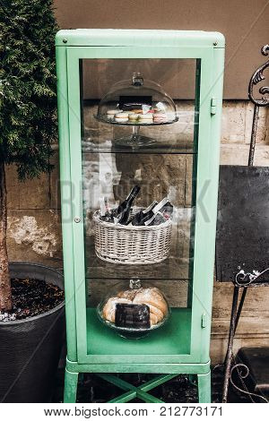 Food Pantry Tray With Macaroons And Wine In Snowy City Streets. European City Preparing For Winter C