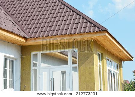 Install metal roof and rock wall insulation with unfinished soffits and fascia boards. House wall insulation. poster