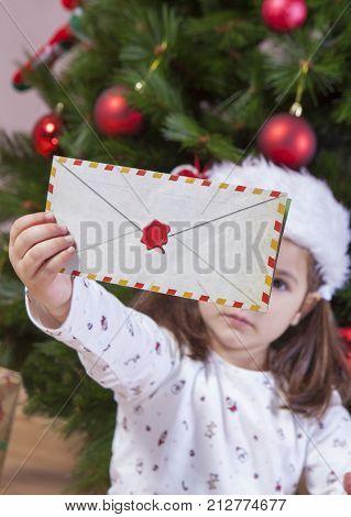 Little girl holds The Santa Letter Envelope. She is sitting beside Xmas Tree at home