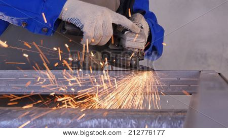 Electric wheel grinding on steel structure in factory Low speed shutter. Employee work with metal or aluminium using special production equipment. Portrait of a worker grinding a metal plate. Industry