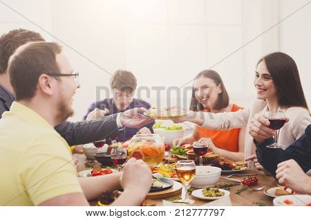 Friends meeting. Group of happy people talking, eating, passing healthy meals at party dinner table in cafe, restaurant.